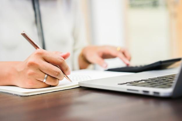 Frauenhandschrift auf notizbuch und drücken auf taschenrechner im büro Premium Fotos