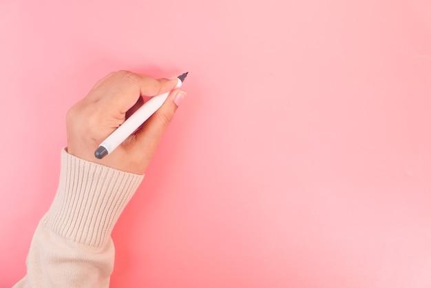 Frauenhandschrift mit stift auf rosa hintergrund. Premium Fotos