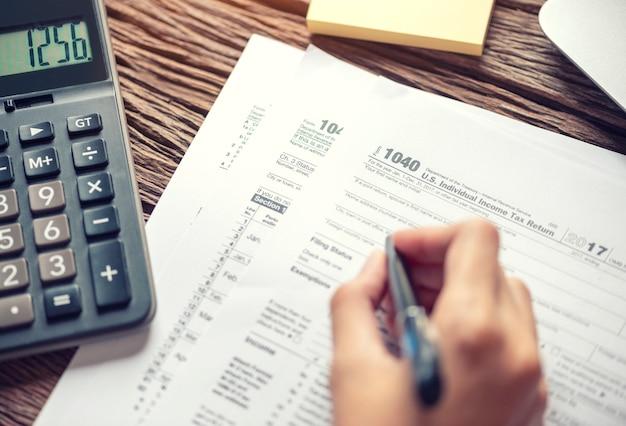 Frauenhandschrift-steuerformular 1040 unter verwendung des taschenrechners individuelles einkommensteuererklärung-zahlungskonzept. Premium Fotos