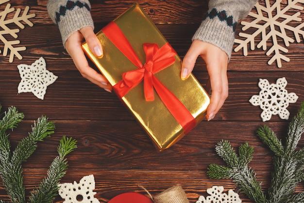 Frauenholding eingewickeltes weihnachtsgeschenk in ihren händen, ansicht von oben Premium Fotos