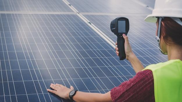 Fraueningenieur, der wärmebildkamera verwendet, um temperaturhitze des sonnenkollektors zu überprüfen Premium Fotos