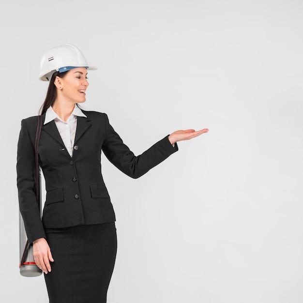 Fraueningenieur im sturzhelm, der mit der hand darstellt Kostenlose Fotos