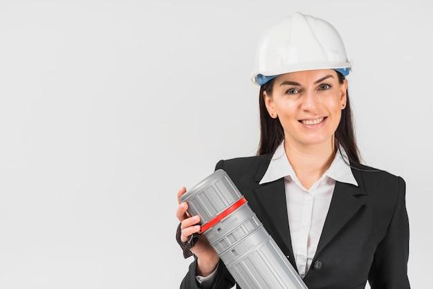 Fraueningenieur im weißen sturzhelm, der rohr hält Kostenlose Fotos