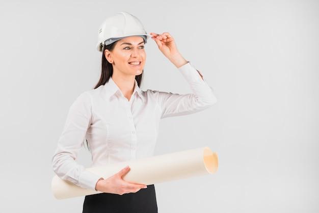 Fraueningenieur im weißen sturzhelm mit whatman-papier Kostenlose Fotos