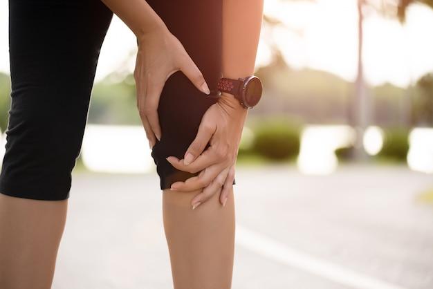 Frauenläufer-gefühlsschmerz auf ihrem knie im park. Premium Fotos