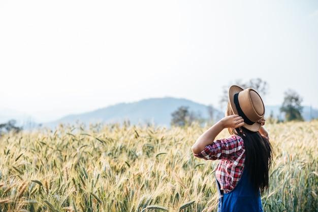Frauenlandwirt mit dem gerstenfeld, das jahreszeit erntet Kostenlose Fotos
