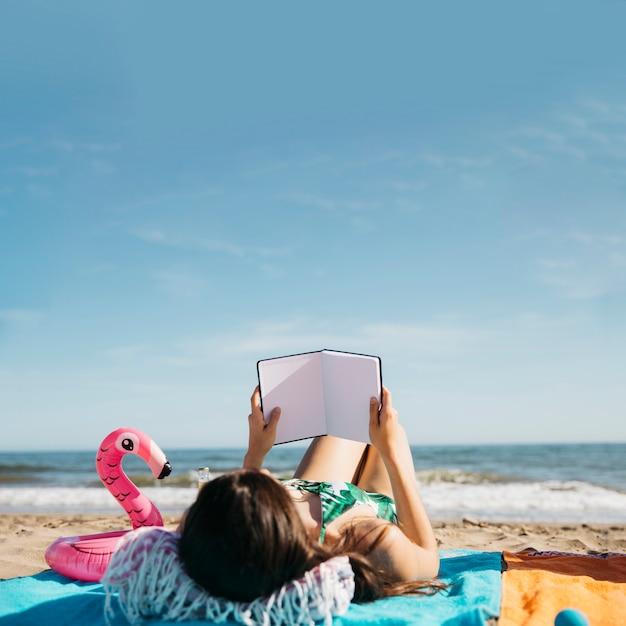 Frauenlesebuch am strand Kostenlose Fotos