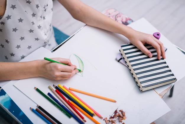 Frauenmalerei auf papier bei tisch mit satz bleistiften und notizbuch Kostenlose Fotos