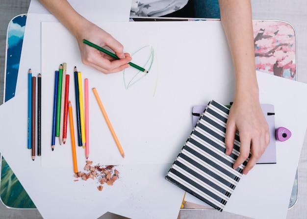 Frauenmalerei auf papier bei tisch mit satz bleistiften Kostenlose Fotos