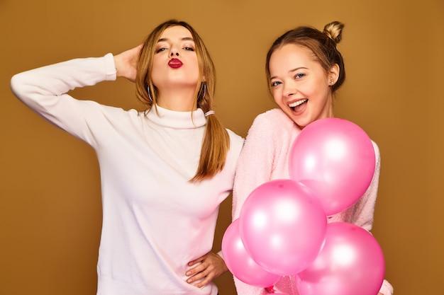 Frauenmodelle mit rosa luftballons auf goldener wand Kostenlose Fotos