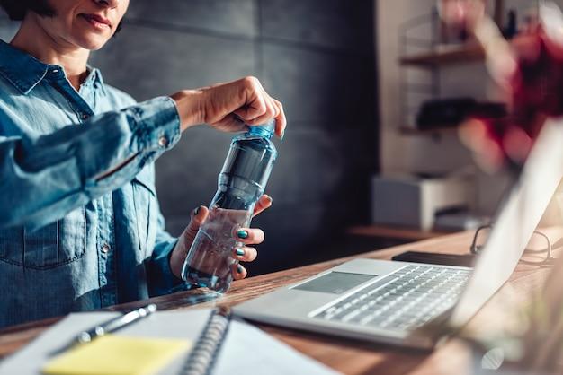 Frauenöffnungsflasche wasser im büro Premium Fotos