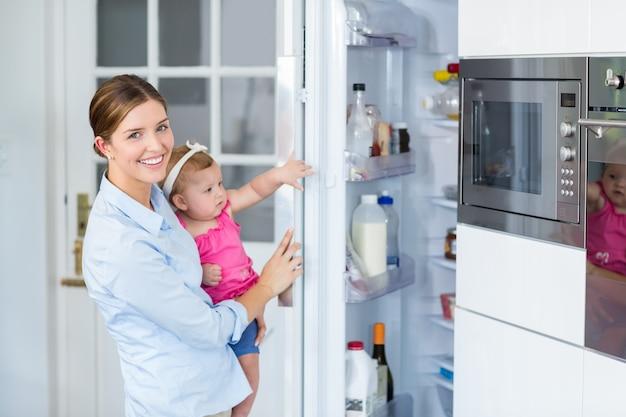 Frauenöffnungskühlschrank beim tragen des babys Premium Fotos
