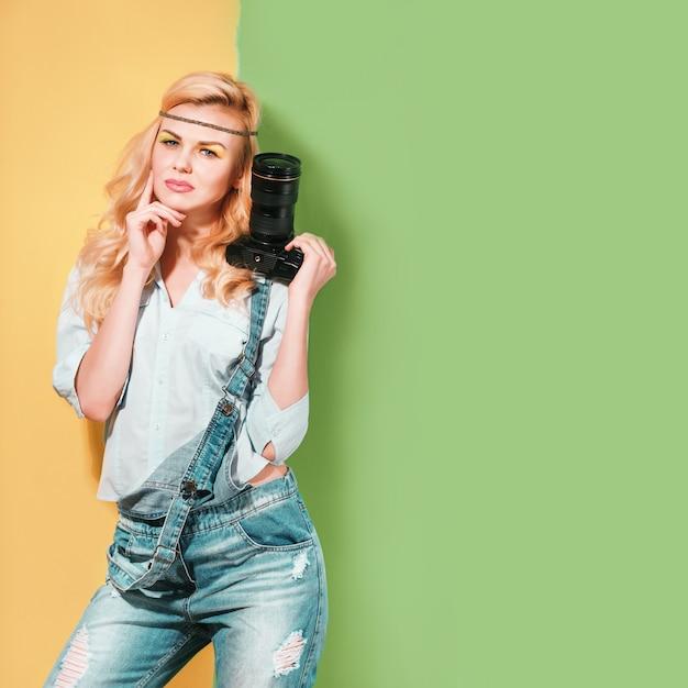 Frauenphotograph, der schüsse auf einer hellen farboberfläche an einem sonnigen tag macht Premium Fotos