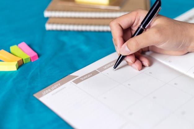 Frauenplanungsagenda und -zeitplan unter verwendung des kalenderereignisplaners Premium Fotos