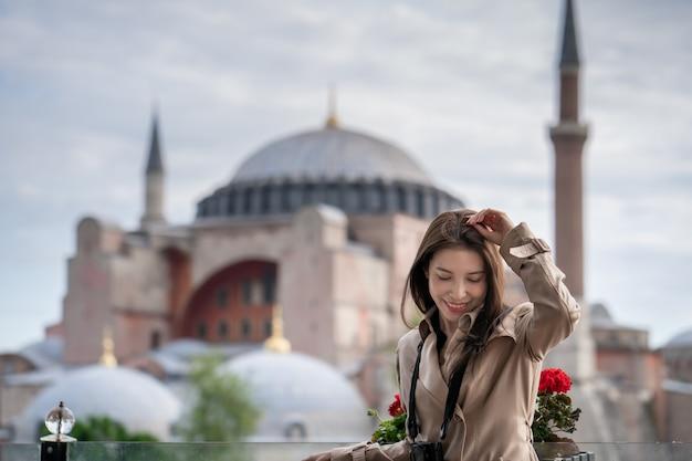 Frauenporträt, das in istanbul nahe berühmter islamischer marksteinmoschee hagia sophia sich entspannt. Premium Fotos