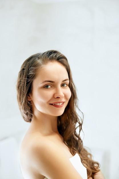 Frauenporträt des nassen haares, gesundes hautpflegekonzept des schönheitshaars, schönes modell mit nassem haar im badezimmer. Premium Fotos