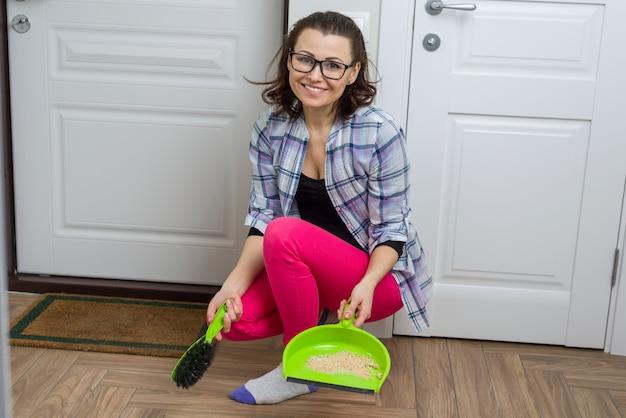 Frauenreinigungsboden mit besen- und staubwanne Premium Fotos