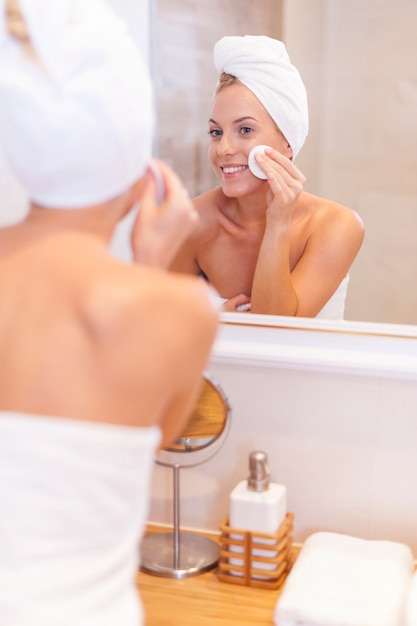 Frauenreinigungsgesicht vor dem spiegel Kostenlose Fotos
