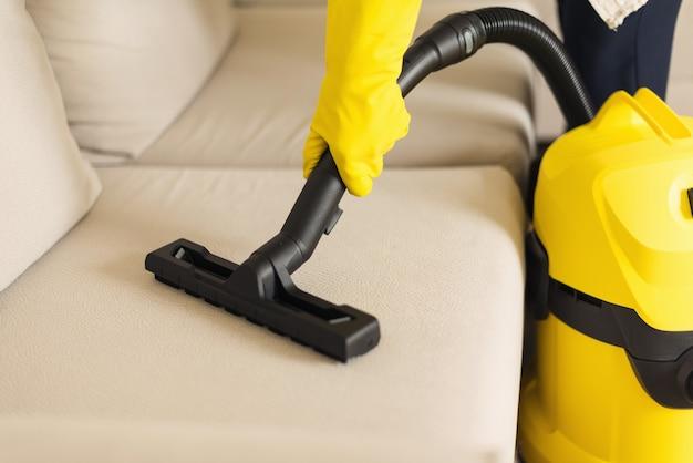Frauenreinigungssofa mit gelbem staubsauger. kopieren sie platz. sauberes konzept Premium Fotos
