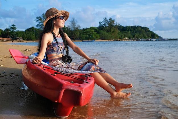 Frauenreisender, der auf dem kajakboot sitzt und foto für ansicht des meeres im urlaub macht. Premium Fotos