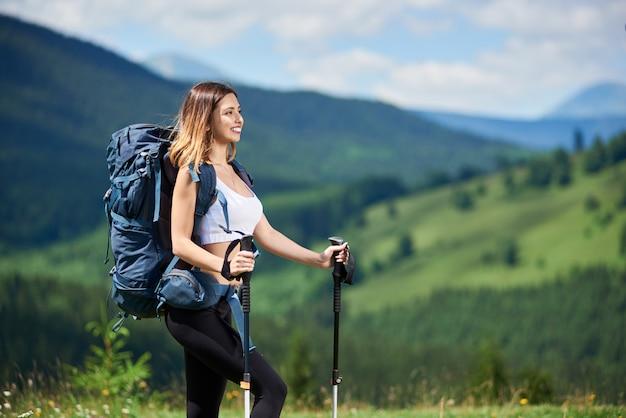 Frauenreisender, der auf die oberseite eines hügels wandert Premium Fotos