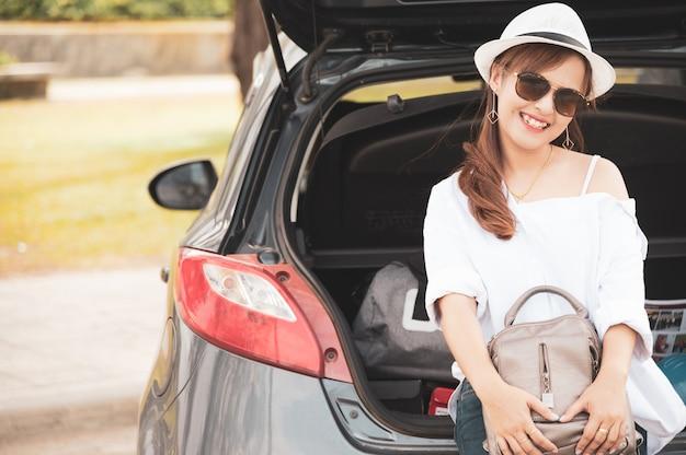 Frauenreisender, der auf hatchbackauto sitzt Premium Fotos