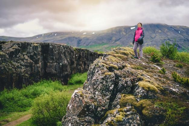Frauenreisender, der durch islandlandschaft wandert. Premium Fotos
