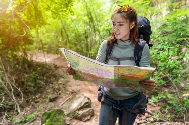 Frauenreisender mit dem rucksack und karte, die richtungen in den wald suchen Premium Fotos