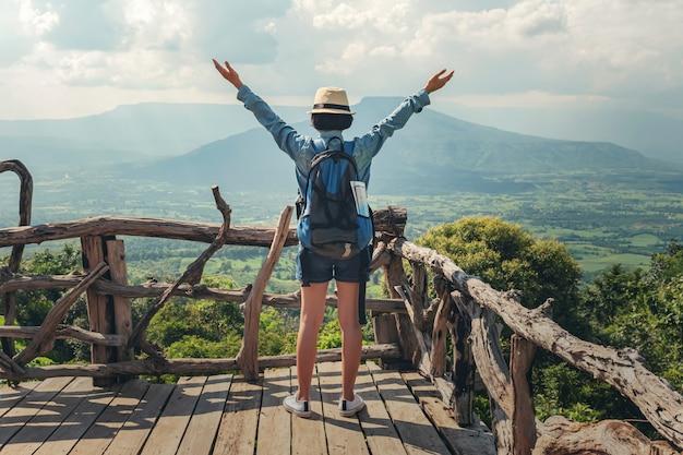 Frauenreisender mit rucksack ansicht und glückliche freiheit an den bergen genießend Premium Fotos