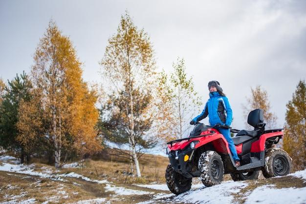 Frauenreiten auf einem roten quadbike atv auf schneebedecktem hügel gegen herbstnatur Premium Fotos