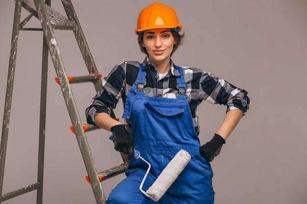 Frauenreparaturmeister mit strichleiter in einer uniform lokalisiert Kostenlose Fotos