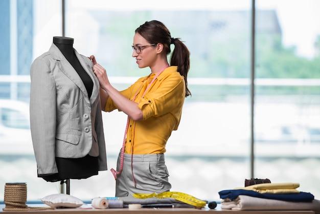 Frauenschneider, der an neuer kleidung arbeitet Premium Fotos