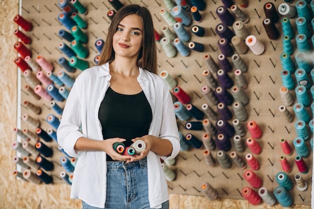 Frauenschneider, der threads an einer fabrik wählt Kostenlose Fotos