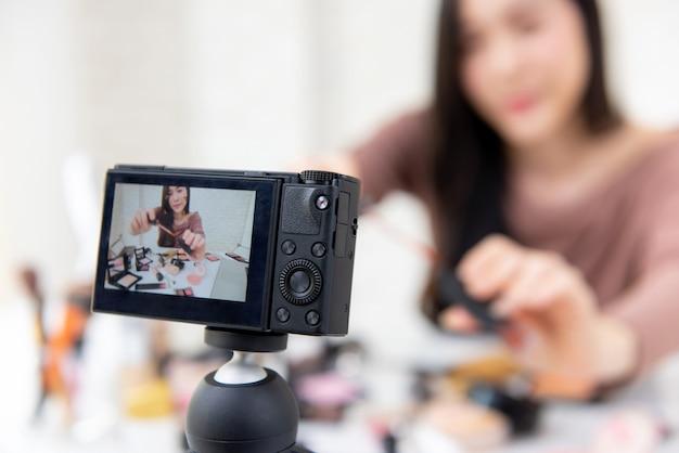 Frauenschönheit vlogger, die kosmetisches make-uplernprogramm mit kamera aufzeichnet Premium Fotos