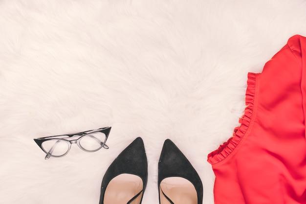 Frauenschuhe mit rock und gläsern auf decke Kostenlose Fotos
