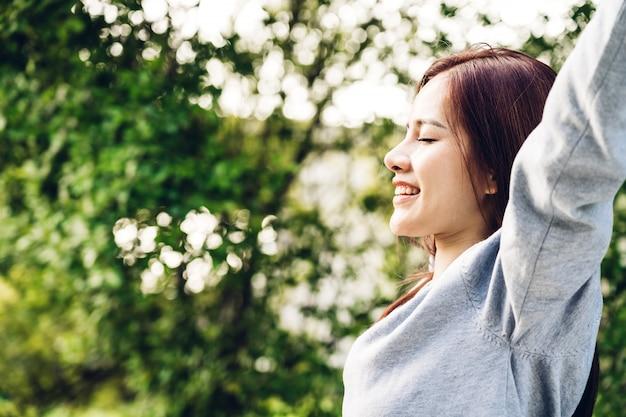 Frauenstellung dehnen ihre arme entspannen sich und genießen mit naturfrischluft Premium Fotos