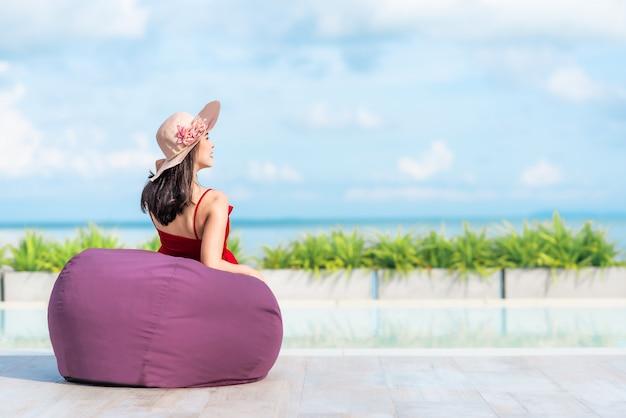 Frauentourist, der auf bohnentasche durch das pool im hotel sich entspannt Premium Fotos