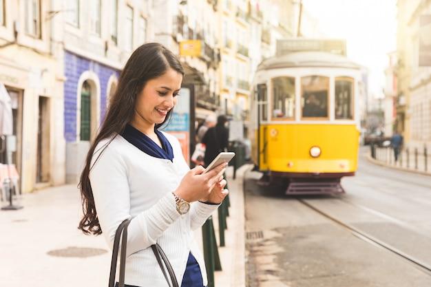 Frauentourist in lissabon tramfahrplan auf ihrem smartphone überprüfend Premium Fotos