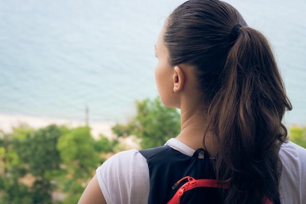 Frauentourist steht auf einem hügel auf dem strand und starrt in den abstand an Premium Fotos
