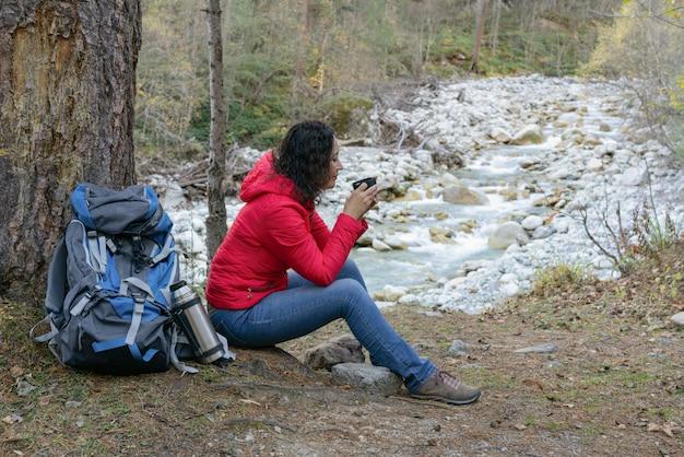Frauentourist trinkt kaffee auf einem halt im wald durch den fluss. Premium Fotos
