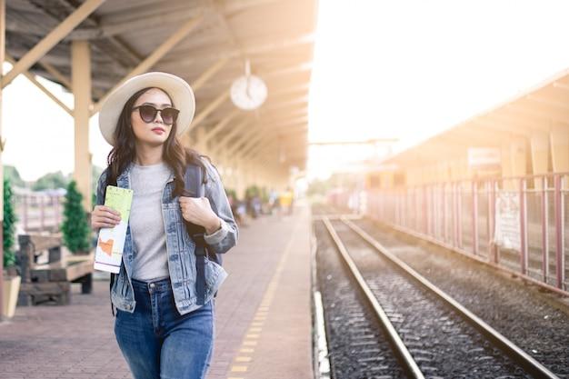 Frauentouristen, die eine tasche der schwarzen gläser tragen, einen hut tragen und eine karte am bahnhof halten. Premium Fotos