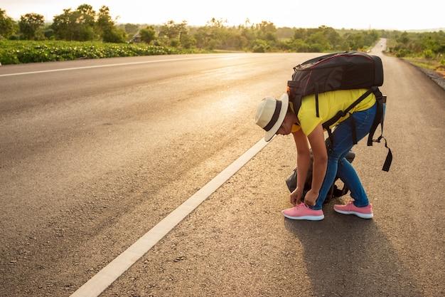 Frauentouristen, welche auf der autobahn die turnschuhe binden Premium Fotos