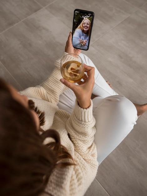 Frauenvideo, das freunde in quarantäne mit getränk anruft Kostenlose Fotos