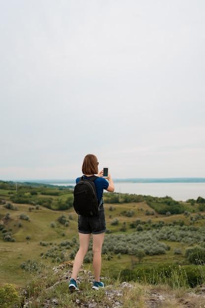 Frauenwanderer, der foto mit smartphone am hügelgipfel nimmt. Kostenlose Fotos