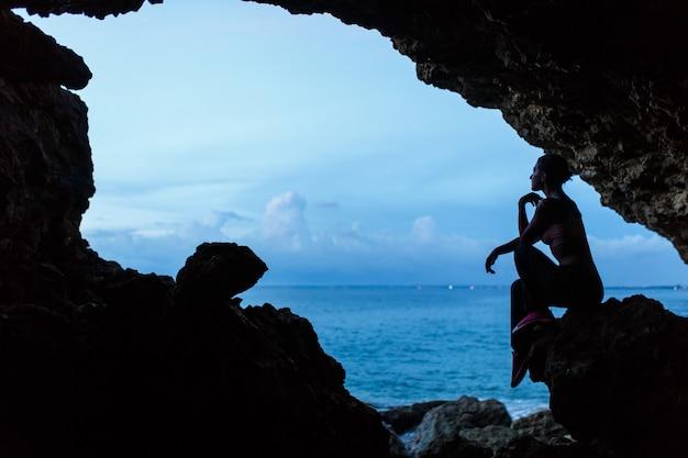 Frauenwartezeitsonnenuntergang in balinesse höhle am ozeanstrand. Premium Fotos