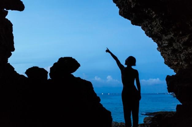 Frauenwartezeitsonnenuntergang in balinesse höhle am ozeanstrand, Premium Fotos