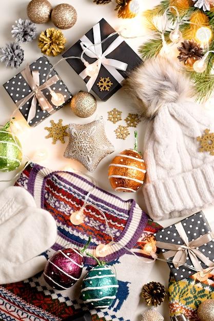 Frauenwinter-kleiderebenenlage mit lichtern, dekorationen, schwarzen geschenkboxen, kiefernkegeln. Premium Fotos