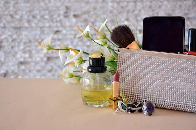 Frauenzusätze, bestehend aus handtaschen, make-up, sonnenbrillen und schmuck Premium Fotos