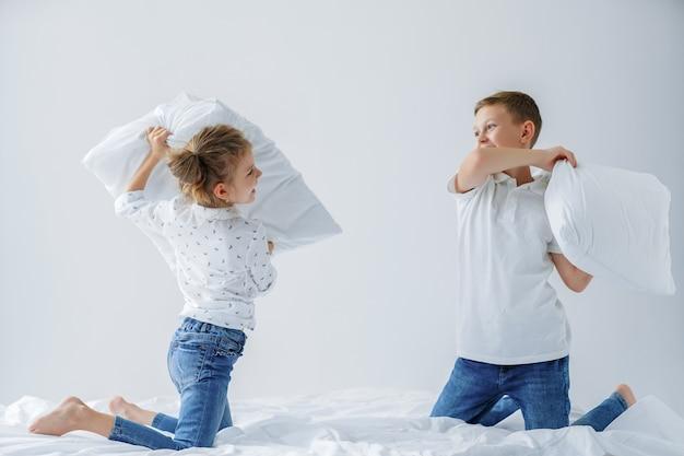 Freches zwillingsmädchen und freundliches kämpfen des jungen inszenierten eine kissenschlacht auf dem bett im schlafzimmer. Premium Fotos