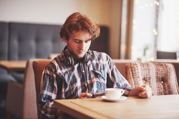 Freiberufler des jungen mannes mit bart in alltagskleidung, der in einem café mit einer tasse kaffee sitzt Kostenlose Fotos